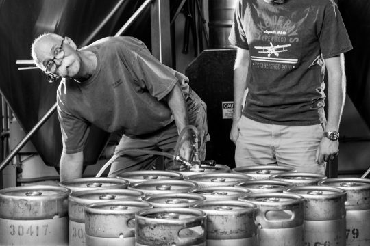 Owners of brewery standing with kegs